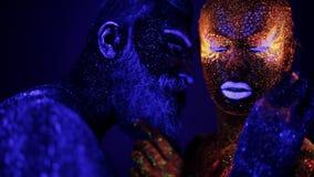 Een man en een vrouw in het ultraviolette licht strelen elkaar Brand en ijs, twee hypostases stock videobeelden