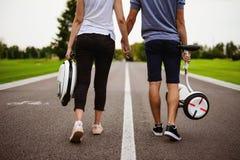 Een man en een vrouw lopen langs de parkweg Zij houden handen en dragen hun monoclean en gyroboard in hun handen Stock Afbeeldingen