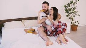 Een man en een vrouw ontwaken in de ochtend, ontbijt in bed stock video