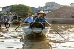 Een man en een vrouw paddelen door de Cai Rang-het drijven markt in C Royalty-vrije Stock Foto