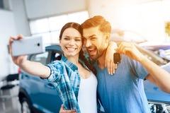 Een man en een vrouw selfie dichtbij hun nieuwe auto royalty-vrije stock afbeelding