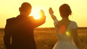 Een man en een vrouw tonen een hart met hun handen bij de zonsondergang van de gouden zon Minnaars op een romantische reis groeps stock footage
