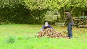 Een man en een vrouw verzamelen en branden bladeren stock footage