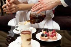 Een man geeft voor een vrouw: giet haar groene thee Op de lijst zijn desserts: tiramisu en gebakjes met verse bessen Zonder gezic stock foto