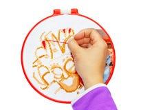 Een man hand die een dwarspatroon op de hoepel (isolate over witte achtergrond) borduren Stock Afbeelding