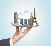 Een man hand houdt een tablet met schetsen van de beroemdste plaatsen in Italië, Groot-Brittannië, Frankrijk en Singapore Het con royalty-vrije illustratie