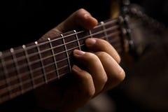 Een man hand op de koorden van de gitaar Stock Afbeeldingen