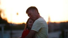 Een man koestert en kust zijn geliefde vrouw Een vrouw vertelt hem iets stock footage
