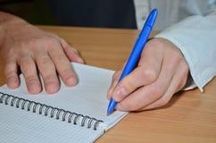 Een man linkerhand in een wit overhemd schrijft de tekst met een blauwe pen in een notitieboekje op een houten lijst stock foto