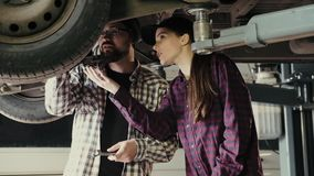 Een man, een mentor, verklaart aan een vrouw, een beginner bij een benzinestation, de principes van reparatie en onderhoud van au stock video