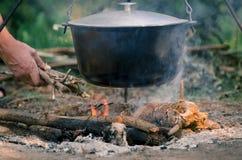 Een man' s de hand ontsteekt een brand onder een pan, welke tribunes op een brand stock foto's