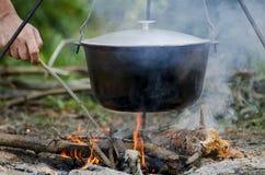 Een man& x27; s de hand ontsteekt een brand onder een pan, welke tribunes op een brand royalty-vrije stock foto
