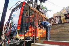 Een man stokvoering de reiziger van de kabelwagen na eind van de dienst bij het gezichtspunt van Meerkawaguchi, Japan stock afbeeldingen