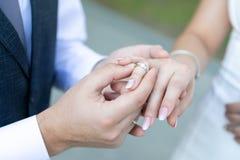 Een man in een vest en de band die een gouden trouwring dragen aan een vrouw in een huwelijk kleden zich op de ringvinger stock foto's