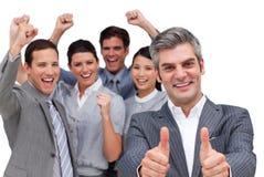 Een manager met duimen die met zijn team opstaan stock foto's