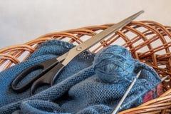 In een mand leg rollen van garen, breinaalden en scissors_ stock fotografie