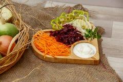 Een mand met gehele groenten en een plaat met gehakte groenten op een achtergrond van het canvas grijs-bruin Het concept van het  royalty-vrije stock foto