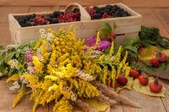 Een mand met rijpe bessen en een boeket van ingediende bloemen op een houten die oppervlakte wordt met heupen en de herfst wordt  Stock Foto's