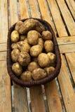 Een mandhoogtepunt van aardappels op houten lijst Stock Afbeelding