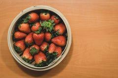 Een mandhoogtepunt van mooie aardbeien bovenop een houten lijst royalty-vrije stock foto