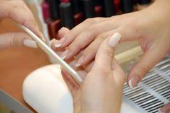 Een manicure is in een schoonheidssalon stock afbeelding
