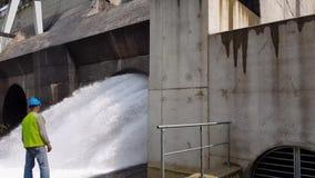 Een mannelijke arbeider bevindt zich voor een stroom van water van een hydro-elektrische turbine stock video