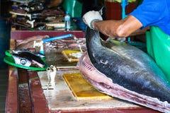 Een mannelijke arbeider bij de vissenmarkt in Mannetje, de Maldiven, die een grote tonijnvis snijden stock fotografie