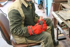 Een mannelijke arbeider een lasser in een beschermend masker last een metaalpijp bij een lassenpost in een workshop bij een metal stock afbeeldingen