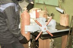 Een mannelijke arbeider op een grote metaal industriële ondeugd herstelt een rode brandblusapparaatcilinder in een workshop bij d royalty-vrije stock foto's