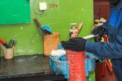 Een mannelijke arbeider op een grote metaal industriële ondeugd herstelt een rode brandblusapparaatcilinder in een workshop bij d stock afbeelding