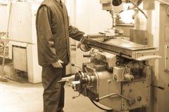 Een mannelijke arbeider werkt aan een grotere de slotenmakerdraaibank van het metaalijzer, equi stock fotografie