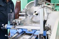 Een mannelijke arbeider werkt aan een grotere de slotenmakerdraaibank van het metaalijzer, materiaal voor reparaties, het metaalw stock foto