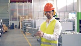 Een mannelijke arbeider werkt met zijn gadget bij een pakhuis, die speciale hoed en glazen dragen 4K stock video