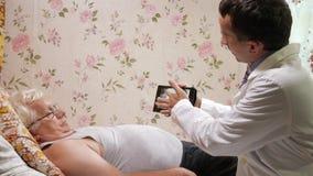 Een mannelijke arts bezoekt thuis een patiënt Het toont de resultaten van de Röntgenstraal op een tabletcomputer De man ligt op stock video
