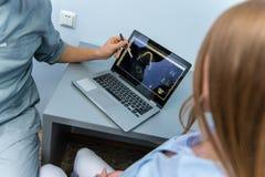 Een mannelijke arts en een meisjespati?nt zitten dichtbij laptop en het spreken royalty-vrije stock fotografie