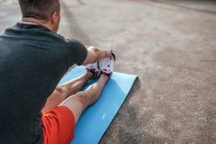 Een mannelijke atleet die gymnastiek die op mat doen, spieren, opleidende de zomerstad op sportterrein uitrekken Actieve opleidin stock afbeelding