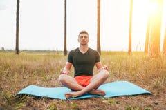 Een mannelijke atleet zit in een lotusbloempositie, rust en mediteert na gymnastiek In de zomer in het park op een sportenmat royalty-vrije stock foto's