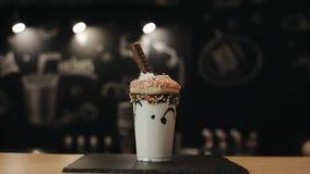 Een mannelijke baristahand die een stro zetten in een buitenissige schok met een doughnut, slagroom, en een chocoladereep stock footage