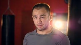 Een mannelijke bokser glimlacht en buigt zijn hoofd aan kanten stock video