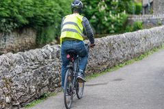 Een mannelijke fietser berijdt een fiets in volledig veiligheidstoestel - Helm, hoog zichtjasje, fietslichten stock afbeeldingen