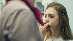 Een mannelijke grimeur zet op samenstelling een jonge vrouw De meester vertelt over make-up voor een groep meisjes Hoofdklasse stock videobeelden