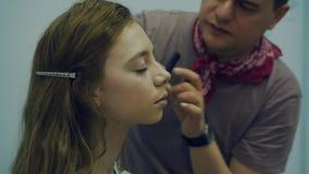 Een mannelijke grimeur zet op samenstelling een jonge vrouw De meester vertelt over make-up voor een groep meisjes Hoofdklasse stock video