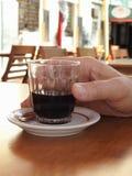 Een mannelijke hand die een glaskop met koffie, op een openluchtbarlijst houden stock fotografie