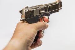 Een mannelijke hand houdt een stuk speelgoed kanon dat op een het vechten wapen lijkt Stock Foto's