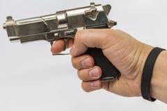 Een mannelijke hand houdt een stuk speelgoed kanon dat op een het vechten wapen lijkt Royalty-vrije Stock Afbeeldingen
