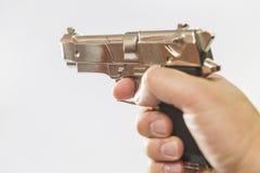 Een mannelijke hand houdt een stuk speelgoed kanon dat op een het vechten wapen lijkt Royalty-vrije Stock Foto's