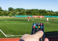 Een mannelijke hand met een afstandsbediening van een Televisie tegen de achtergrond van het voetbalgebied waarop zij voetbal spe stock fotografie