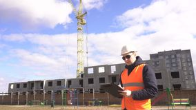 Een mannelijke ingenieur met zwarte glazen in een helm en een signaalvest schrijft en tekens in een tablet bij een bouw neer stock footage