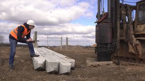 Een mannelijke ingenieur in zwarte glazen controleert de kwaliteit van concrete stapels het drijven in de reden tot de stichting stock videobeelden