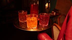 Een mannelijke kelner die de cocktail op het dienblad zetten en brengt een alcoholcocktails aan een bedrijf van jonge vrienden stock footage